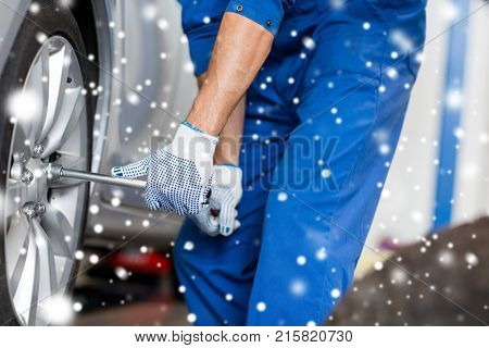 car service, repair, maintenance and people concept - auto mechanic man with electric screwdriver changing tire at workshop over snow