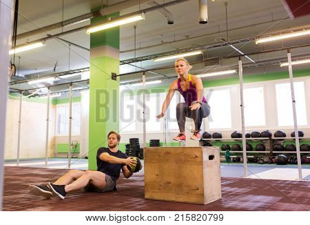 fitness, sport, training, exercising and people concept - woman and man with medicine ball doing curl ups and box jumps in gym