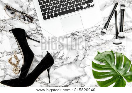 Feminine accessories notebook shoes green monstera leaf on table background. Fashion flat lay for blogger social media