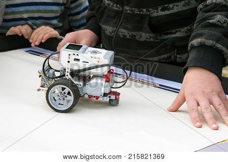 Kropivnitsky, Ukraine - October 7, 2017: Robot Car robotics with remote control. Fan robots with children's hands in the background. School Robotics learning for children. Modern training. Model kits. The hottest gadgets.