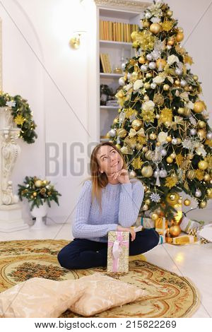 Joyful cute young woman smiling and posing with gift box with bow in hands. Woman in good mood happy with upcoming New Year holidays and shows gift to camera, sitting on carpet on floor in spacious living room with New Year's high decorated pine and firep