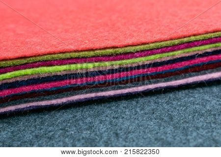 Different color Pile of felt flaps on gray fabric blurred background. Stack of colorful felt flaps on a gray fabric. Handmade creativity crafts sewing needlework background. Selective focus