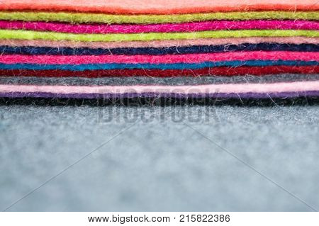 Different color Pile of felt flaps on gray fabric blurred background. Stack of colorful felt flaps on a gray fabric. Handmade creativity crafts sewing needlework background