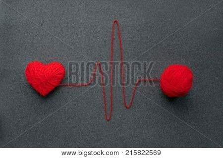 Handmade red yarn ball with heart made of red wool yarn and thread like ECG pattern on a gray woolen fabric background. Red warm heart like a symbol of love. Heart health heartbeat feelings love romance concept