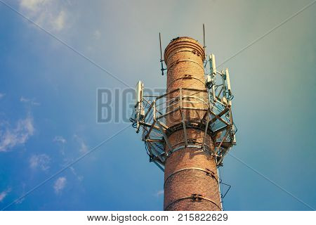 Mobile communication transmitters on a round brick pipe against a blue sky background with sunlight. Mobile phone communication antenna tower