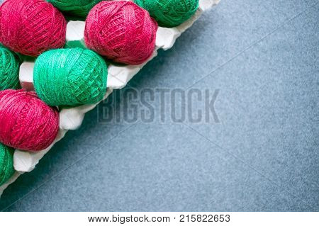 Balls of colored red and green yarn in a paper egg tray. Diagonal frame. Copy space. Skeins of cotton yarn for knitting and creative needlework. Knitting as a kind of cozy needlework.