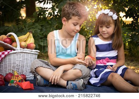 Little Happy Girl And A Boy Are Sitting On A Blanket In The Park And Having A Picnic