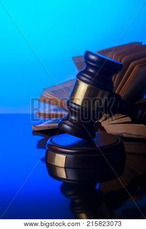 Law and justice concept - law gavel with open old book in background