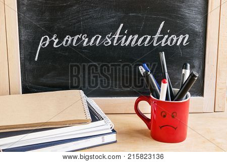 Lettering of word Procrastination on black chalkboard on a background of notepads and diary and a red cup with a sad smile. Business and pischological concept. Self-control and achieving the goal