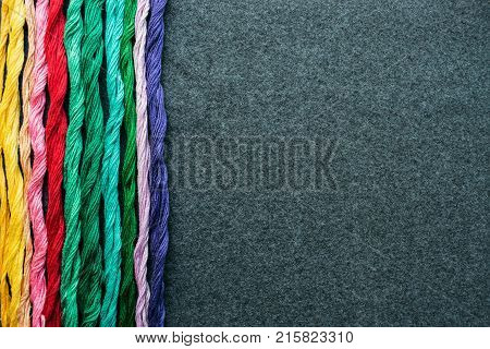 Bright multicolored embroidery thread yarns. Skeins of multicolored embroidery threads on dark felt canvas. Handmade embroidery sewing background