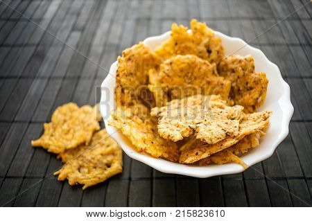 Cheese Chips Snack in a round white bowl on a black wooden background. Grain Free Dippable Crispy Cheddar Cheese Chips Keto & Low Carb. Crunchy chip to snack from cheddar parmesan asiago herbs spices