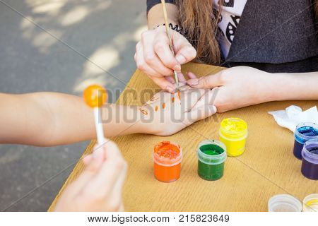 Artist draws a pattern on the child's hand with a brush and watercolor orange paint. Hand painting children activity. Animator draws the painting on the child hand