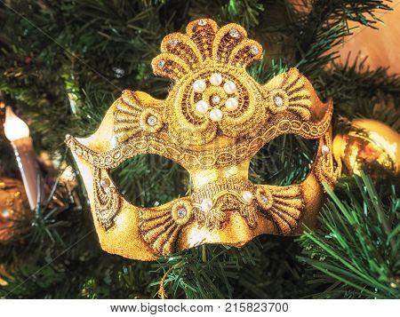 Venetian carnival mask on christmas tree. Christmas and New Year's background. Christmas tree, ball, candle, mask, Christmas decorations.