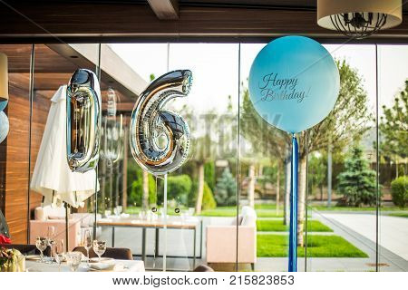 Festively served table for the 16th anniversary. Two figures 1 and 6 on the background of a table with empty glasses.