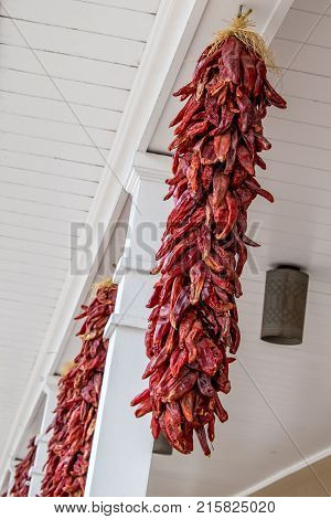 Row of red hot chili peppers hanging to dry on a sidewalk in Santa Fe New Mexico.