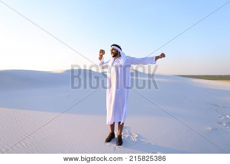 Handsome young Emirate strolls and stretches, spreads hands to sides and rests from city bustle, examines surroundings of wide desert with white sand. Swarthy Muslim with short dark hair dressed in kandura, long, spacious dress made of white unpainted cot