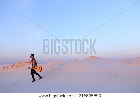Young Muslim male performer and singer walks through sandy desert with guitar in hands, stops and begins to play on spot on musical instrument, rejoices and smiles, sings songs about love on warm summer evening at sunset. Swarthy man with dark hair and sh