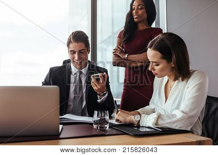 Successful businessman talking on mobile phone while working with his business team. Business man speaking on the phone while working with colleagues in office.