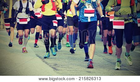 a group of fast runners on the finish line at the end of the marathon in the city with lomography effect