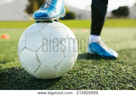 Close up of teenager's legs with a ball on football pitch. Cropped shot of soccer player training on the artificial grass field.