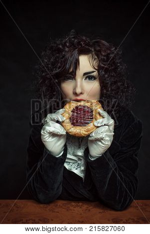 Gothic girl eating sweet bun over dark background