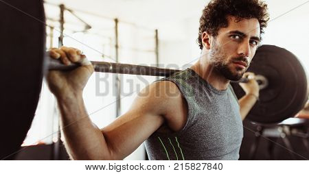 Confident young man exercising with barbell. at fitness center. Male bodybuilder working out with heavy weights at training gym.