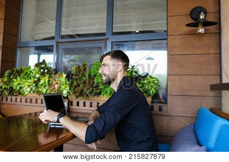 European manager and businessman giving interview about achieving success, working with laptop at table near indoor plants. Handsome man looking at camera has blue eyes, beard and looks happy. Concept of advising how reach prosperity and ways of developme