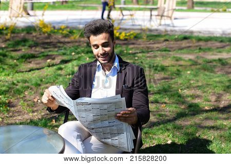 Guy sits on chair near table and reading newspaper. Man has beard, short hair and dimples. Male dressed in black jacket, white jeans and blue shirt. Concept of newspapers advertisement places for reading quite clean parks day off.