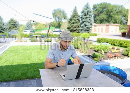 Skilled actuary working with laptop and documents at cafe table. Handsome man dressed in white shirt sitting near green plants on sofa and typing with keyboard. Concept of a person compiling and analyzing statistics, using to calculate insurance risks and