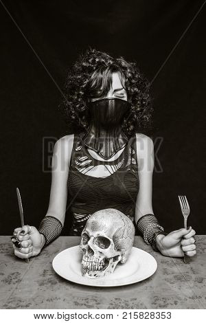 Gothic girl in bdsm mask with skull in her plate over dark background