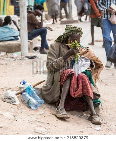 HARAR, ETHIOPIA-MARCH 31, 2017: An unidentified man pulls Qat, a stimulant drug, from a plastic bag in the city of Harar.