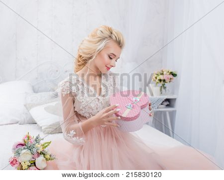 Beauty fashion bride in winter decor with gift box in her hands. Beautiful Bride portrait wedding makeup and hairstyle. Fashion bride model in luxury wedding dress. Beauty girl face gorgeous beauty bride.