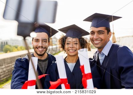 education, graduation, technology and people concept - group of happy international students in mortar boards and bachelor gowns with diplomas taking picture by smartphone selfie stick outdoors