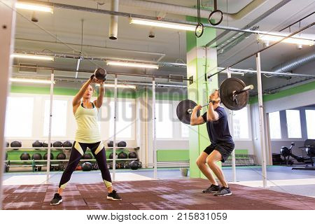 sport, fitness, weightlifting, lifestyle and people concept - man and woman with kettlebell and barbell exercising in gym