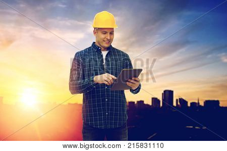 construction, building and technology concept - smiling male builder or manual worker in yellow hard hat with tablet pc computer over city background