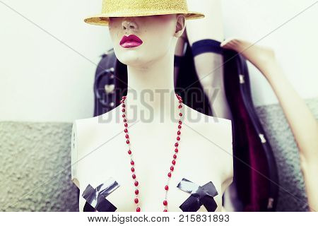 portrait of female dummy with hat in front of composition of various dummy pieces piled in a corner