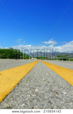 two yellow dividing line on the highway on blue sky background. travel concept