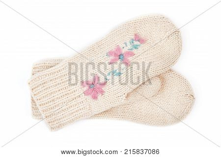Pair of beautiful white hand mittens. Cute female knitted pair of gloves with a pattern of flowers isolated on white background. Female winter hand accessory.