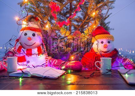 Snowmen Drinking Tea On Terrace Table. Christmas Mood Outside. Bright Lights And Cozy Atmosphere. Wa