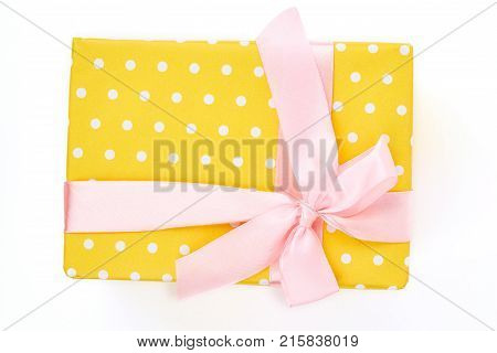 Yello dotted gift box, white background. Box with Christmas present tied with gentle pink satin ribbon isolated on white background, top view.