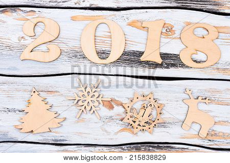 Wooden number 2018 and New Year figures. New Year number from the wooden figures and carved wooden objects of shape of Christmas tree, snowflake, candles, deer on vintage wooden background.