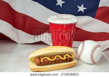 overflowing beer in red cup and baseball with hot dog and American flag background