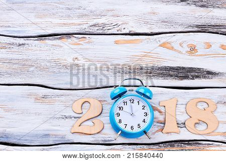 Wooden number 2018, alarm clock, copy space. Twelve o'clock on a blue round alarm clock and show New Year 2018 on wooden background.