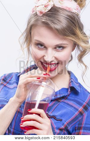 Youth Fashion and Lifestyle Concepts. Happy Laughing Caucasian Blond Girl Posing Drinking Juice Using Straw.Vertical Shot