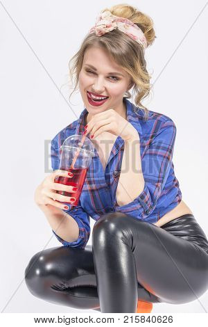 Youth Lifestyle Concepts. Portrait of Happy Smiling Caucasian Blond Woman in latex pants Posing with Cup of Red Juice and Straw. Against White.Vertical Image