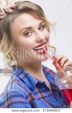 Youth Lifestyle Concepts. Portrait of Happy Smiling Caucasian Blond Woman in Checked Shirt Drinking Red Juice Using Straw. Against White.Vertical Image