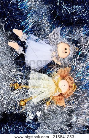 Two Christmas angels on tinsels background. Cute Christmas angel figurines on shiny Christmas garlands background. Merry Christmas and happy New Year.