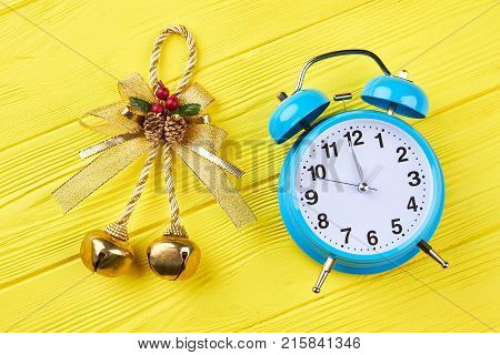 Golden bow with jingle-bell and alarm clock. Two Christmas jingle bells and blue alarm clock on yellow wooden background. New Year and Christmas concept.