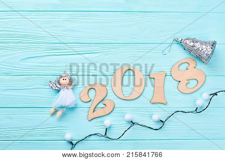 New Year 2018 blue wooden background. New Year 2018 decorations with Christmas lights, angel figurine and silver bell, copy space. Happy New Year 2018.