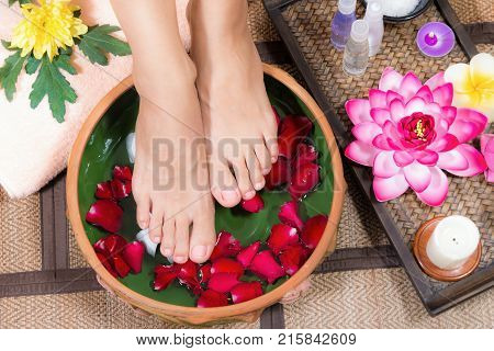 Closeup shot of a woman feet dipped in water with petals in a wooden bowl. Beautiful female feet at spa salon on pedicure procedure.